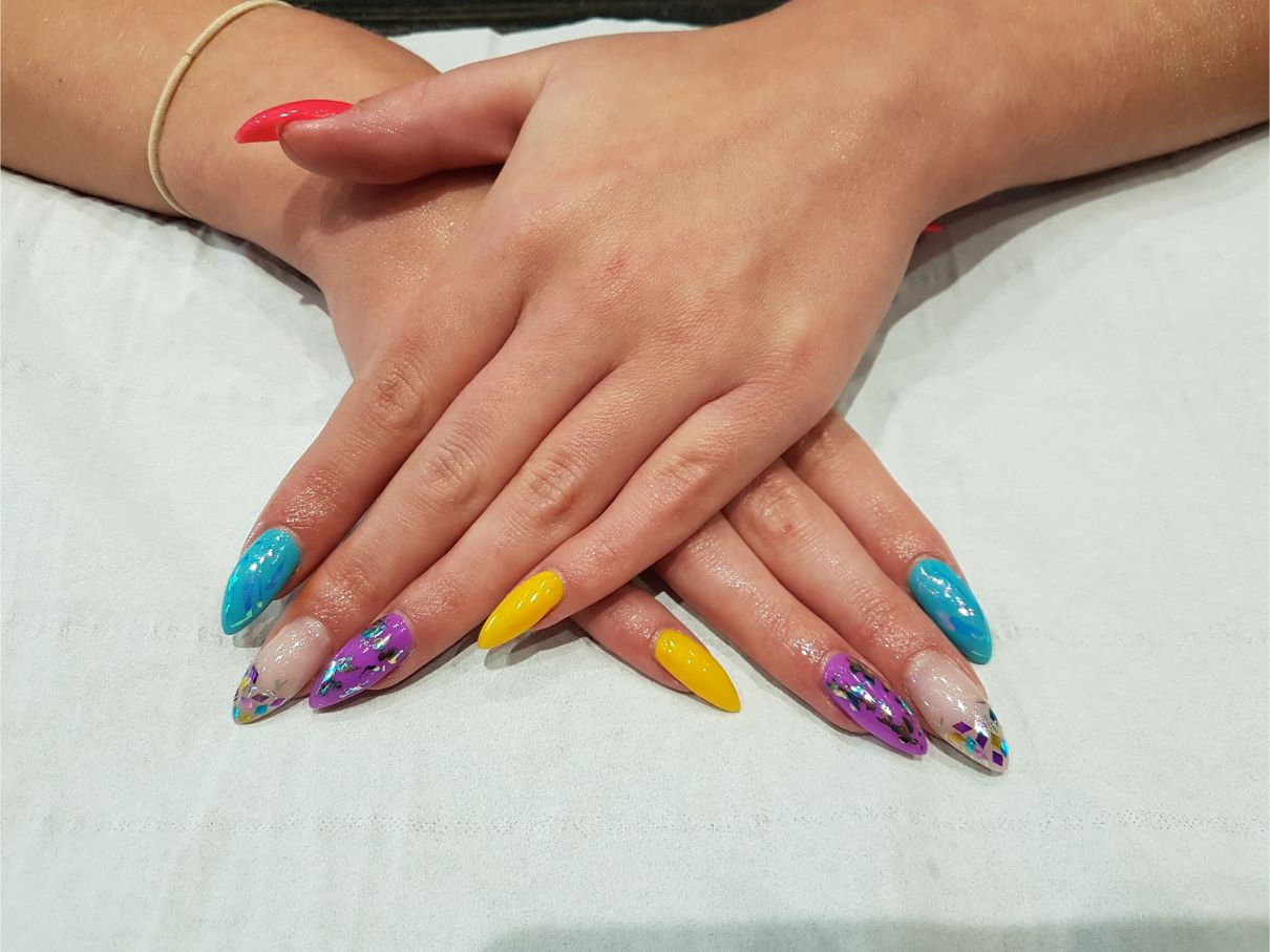 hands with yellow, blue, and purple nail art
