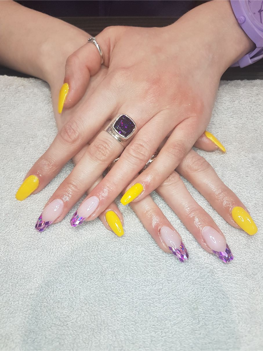 hands with yellow and purple nail art