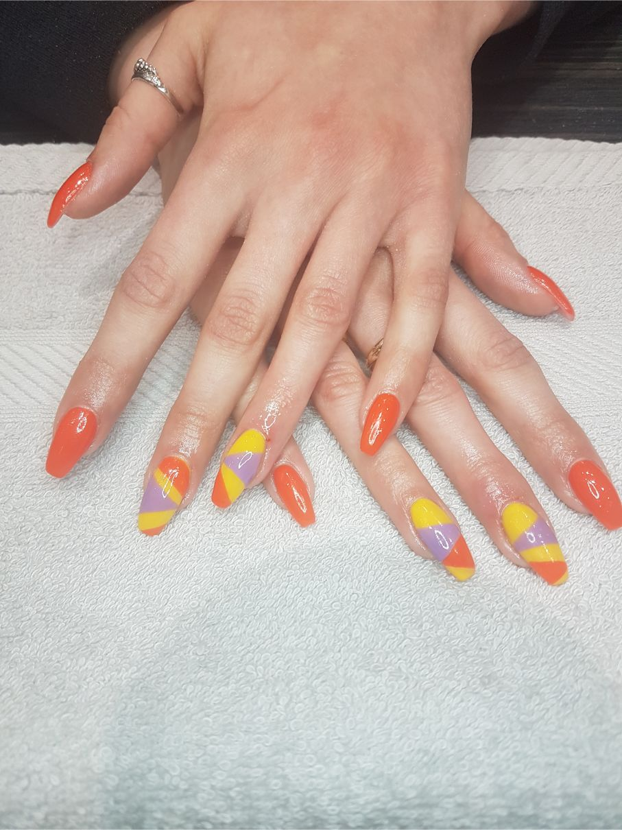 hands with yellow, orange and purple nail art
