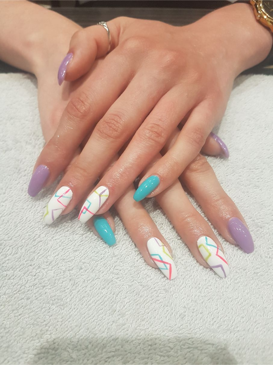 hands with green, white and purple nail art